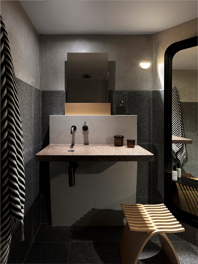 "Terrazzo tiles layered with rendered cement walls lend a dark, sensual appeal to this luxurious [apartment designed by Amber Road](https://www.homestolove.com.au/sydney-penthouse-apartment-by-amber-road-19349|target=""_blank""). The designer says ""An early decision was to leave the cement base and services raw and exposed, with a simple palette of terrazzo, timber and stone."" *Photo: Felix Forest / Styling: Alicia Sciberras / Story: Belle*"
