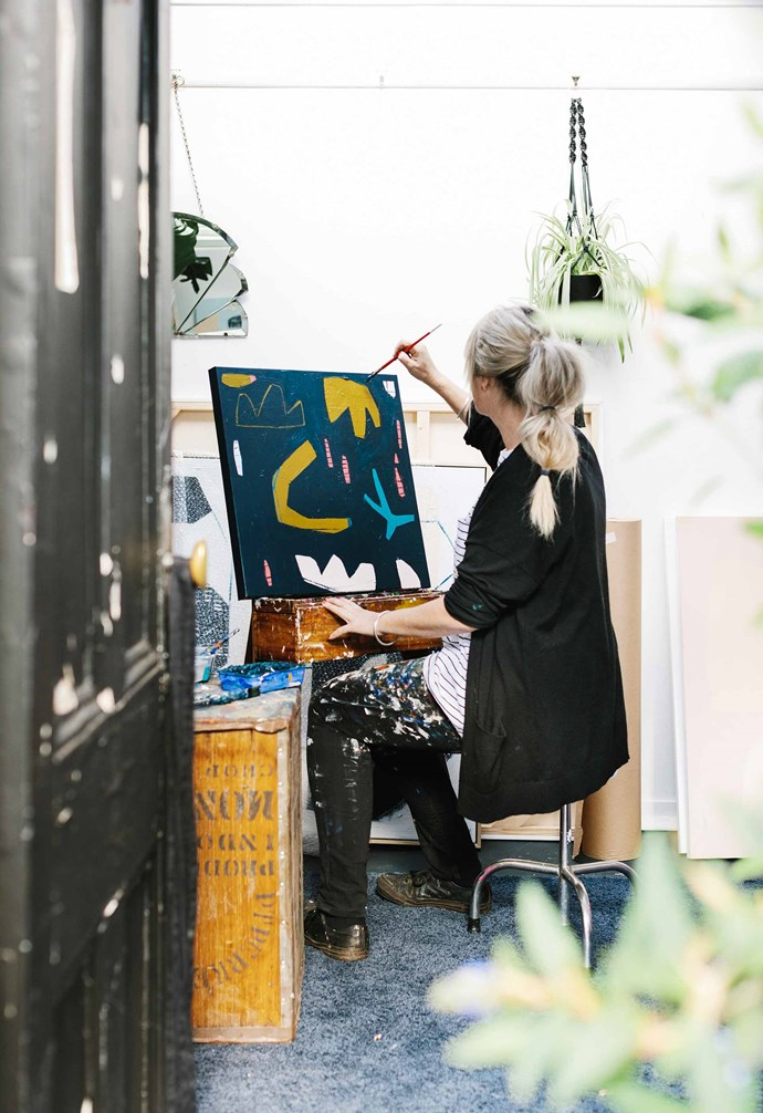 """""""Once I've decided on a complementary palette, I usually add a splash of clash, to create a slightly edgier feel,"""" says Carly. Here, she works on *Carnival* in her studio. *Photography: Marnie Hawson*."""
