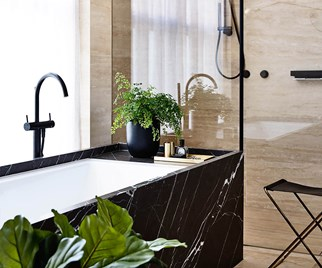 Black marble inset bath tub with indoor plants