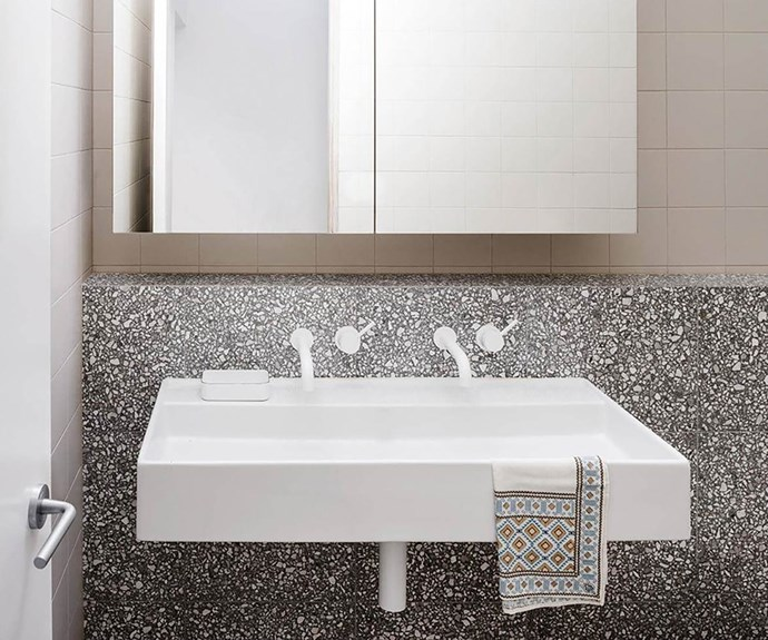 White bathroom sink with terrazzo vanity