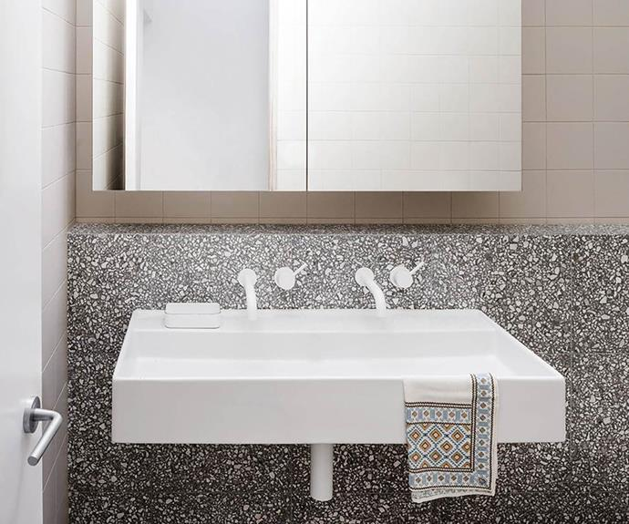 White bathroom sink with terrazzo vanity