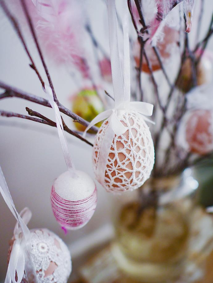 Another way to decorate Christmas eggshells (without the mess of glitter) is to wrap them in lace. Just use craft glue to attach the fabric to the surface of the egg.