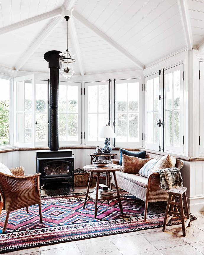 "A small sitting area off the kitchen features a wood stove and a kilim rug from Duncan's parents. The antique Chinese wooden stool is from [Amara Home](https://www.amara.com/au|target=""_blank""