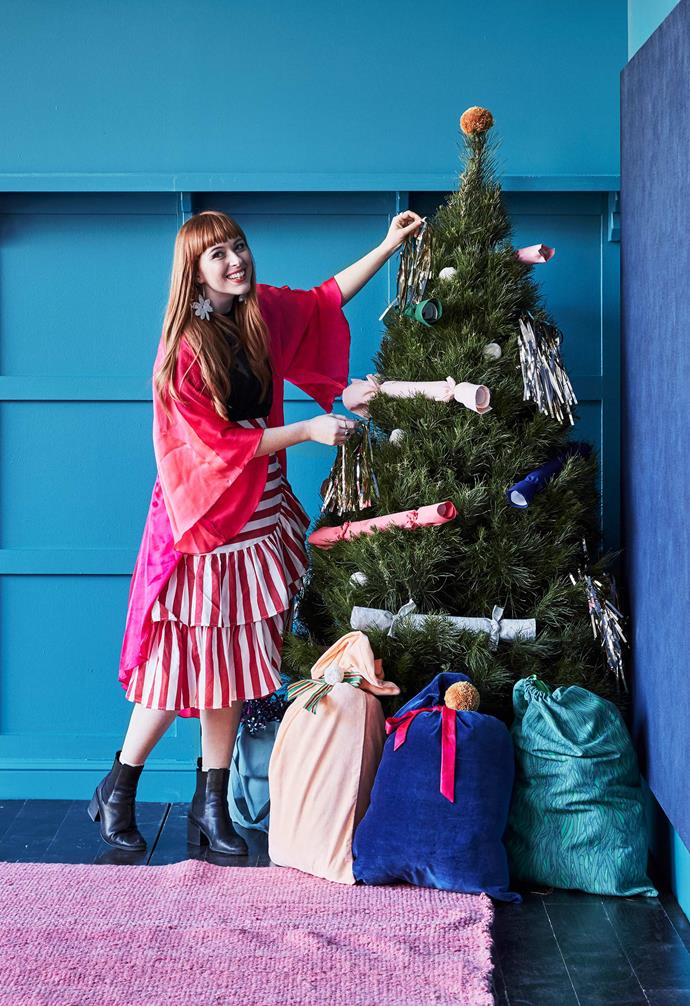 """**Make it: Rachel Burke's tinsel decorations** """"Cut strands loose from tinsel curtain hanging (available from party stores and craft shops) into 40cm lengths and pile them into thick bunches. Secure each bunch around the middle with sticky tape, and cover the tape by winding an extra strand of tinsel around it, and tying it off in a knot to secure it.""""<br><br>**Get the look**: *Christmas tree, Dural Christmas Tree Farm. Tote in sky blue, $79, French Cargo. Pillowcases in peach and navy (used as sacks), $49.95 each, Castle. 'Hakone' fabric by Patricia Braune (made into Santa sack), $82/metre. *Impermanence III* artwork by Celia Gullett, POA.*"""