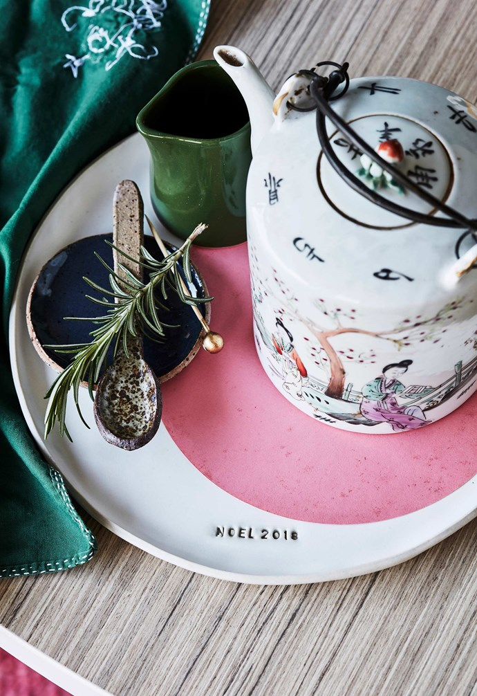"**Megan's tip** ""A little bit of customisation goes a long way. This year, I'm having platters and spoons stamped by a local ceramicist, Splendid Wren Ceramics, to make it feel special."" <br><br>**Get the look**: *Napkin, from a selection at Seasonal Concepts. 'Noel 2018' dinner plate, $65, 'Emu' condiments dish, $45/set of 3, speckled teaspoon, $15, Splendid Wren Ceramics. 'Penguin' jug, $22.95, Robert Gordon. Teapot, $120, Water Tiger. *"
