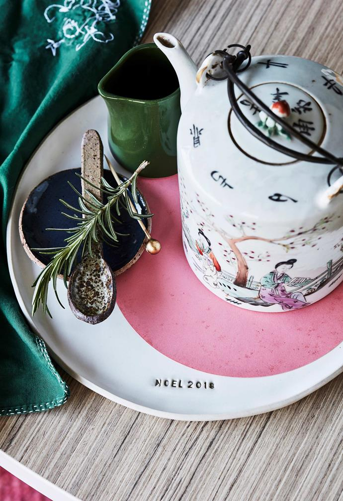 """**Megan's tip** """"A little bit of customisation goes a long way. This year, I'm having platters and spoons stamped by a local ceramicist, Splendid Wren Ceramics, to make it feel special."""" <br><br>**Get the look**: *Napkin, from a selection at Seasonal Concepts. 'Noel 2018' dinner plate, $65, 'Emu' condiments dish, $45/set of 3, speckled teaspoon, $15, Splendid Wren Ceramics. 'Penguin' jug, $22.95, Robert Gordon. Teapot, $120, Water Tiger. *"""