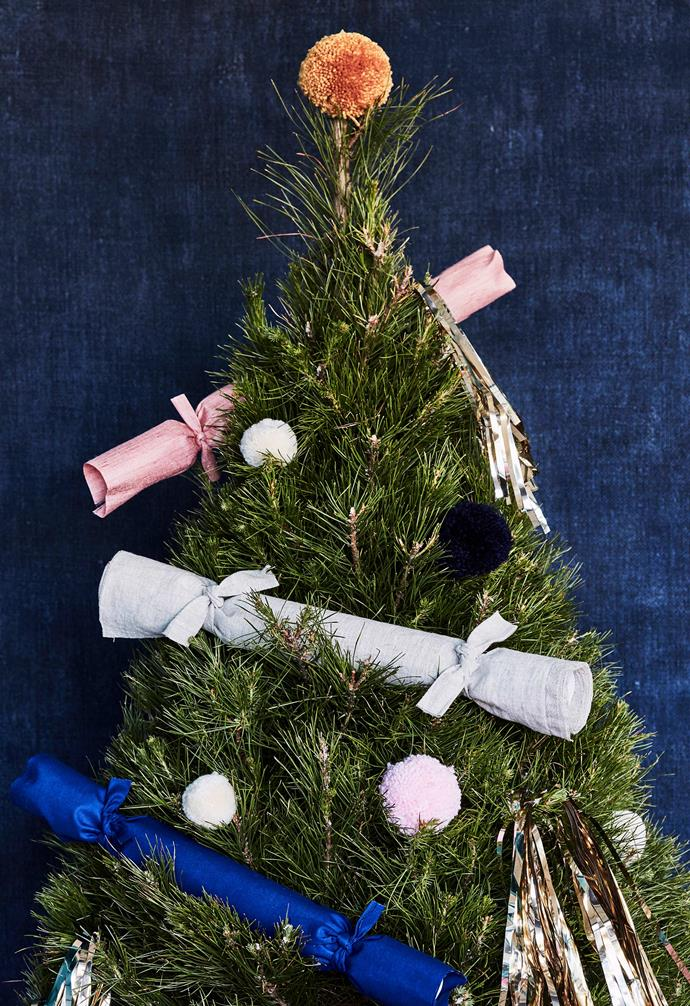 """**Megan's tip** """"Use bags you already have in lieu of wrapping paper. Cloth tote bags are ideal to use as second gifts and replacement wrapping. Make your own bespoke bags with simple sewing and ribbon ends. Or use the store-supplied tissue paper and just add a card.""""<br><br>**Get the look**: *Christmas tree, Dural Christmas Tree Farm. Tote in sky blue, $79, French Cargo. 'Golden Fleece' jacket (in tote), $450, by Rachel Burke.*"""