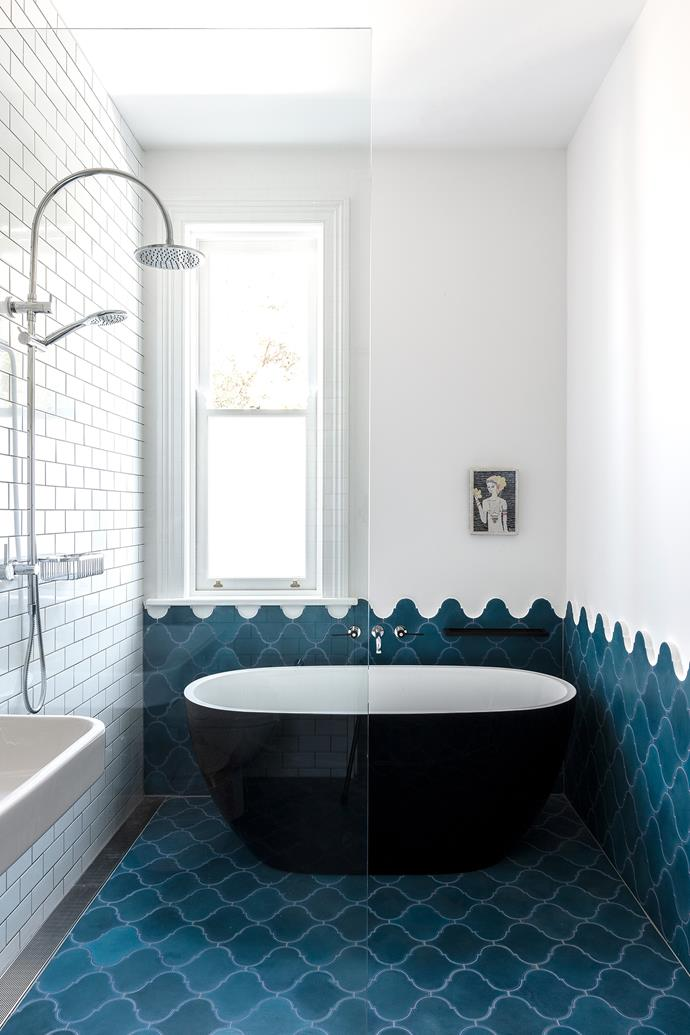A compact freestanding bathtub in black is the focal point of the room.