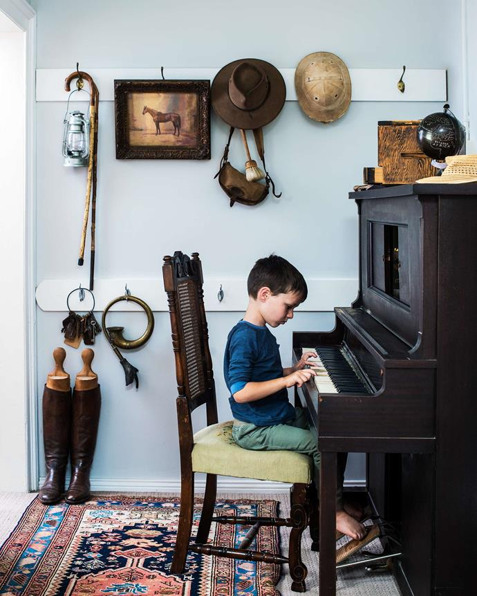 Jack sits at the pianola. The painting is of Valicare, a champion mayor who belonged to Patrick Hamilton Osborne, the property's original owner.| *Photography: Brigid Arnott | Styling: Kristen Wilson*
