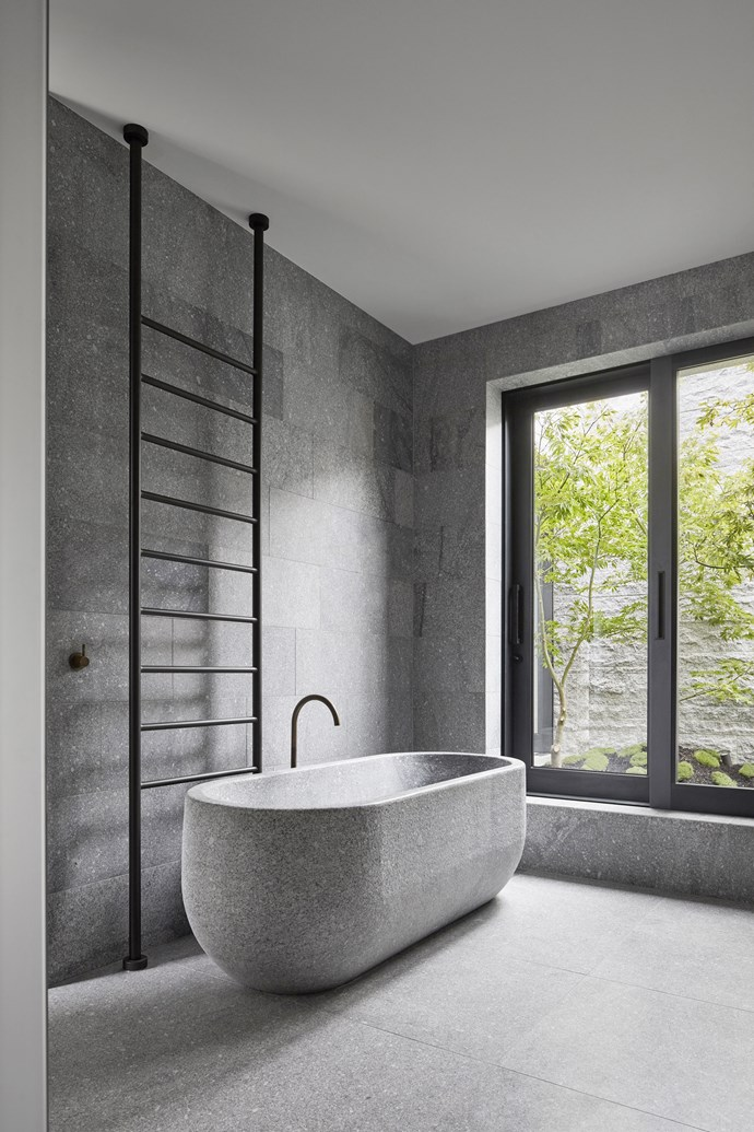 """The bath was custom-made by B.E. Architecture and carved from solid granite. Behind the bath is a heated 'Floor to Ceiling' towel rail from [Rogerseller](https://www.rogerseller.com.au/