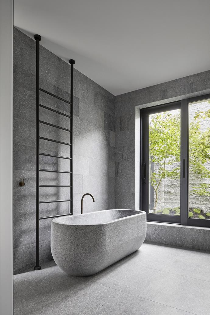 "The bath was custom-made by B.E. Architecture and carved from solid granite. Behind the bath is a heated 'Floor to Ceiling' towel rail from [Rogerseller](https://www.rogerseller.com.au/|target=""_blank""