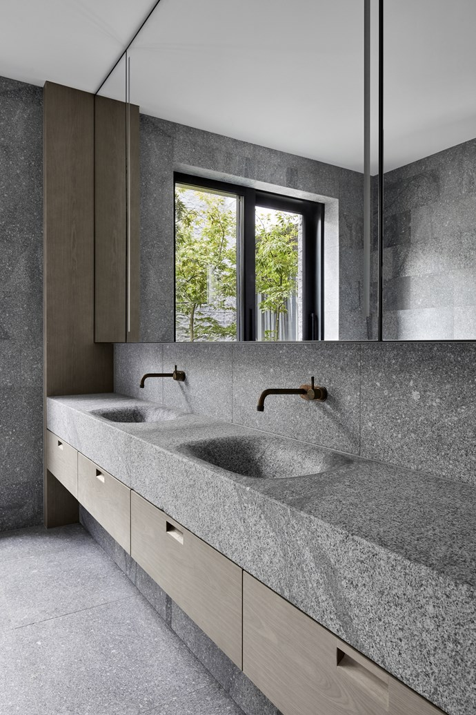 """The mirror above the vanity was custom-made with built-in recessed lights. The basins were carved from solid 'Fallow' granite from [Eco Outdoor](https://www.ecooutdoor.com.au/products/natural-stone-flooring/granite-paving/fallow-2/