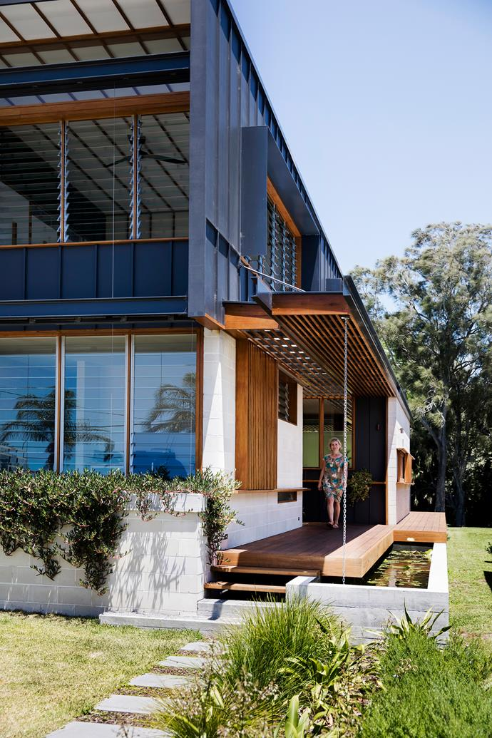Homeowner Sharon Auld at the inviting entrance to her eco-conscious four-bedroom home. Kiln-dried blackbutt features on the vertical surfaces of the house and tallowwood decking wraps around it. The garden is planted with waterwise trees, plants and grasses.