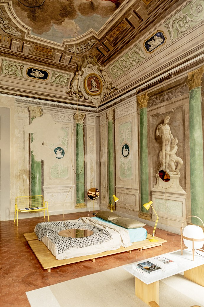 In the guest room, original wall frescoes that date back to the Renaissance remain intact. It's reserved for high-profile artists and has the potential to be used for photoshoots and installations. The yellow bench and marble coffee table are by Numeroventi.