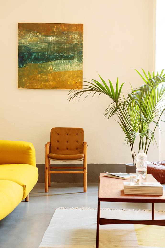 """To counteract the overwhelming architecture, I went for contemporary and sober touches,"" says homeowner Martino. The shared living room is furnished with a coffee table and a vintage leather chair. The artwork is by [Lorenzo Brinatia](https://www.numeroventi.it/lorenzo-brinati/