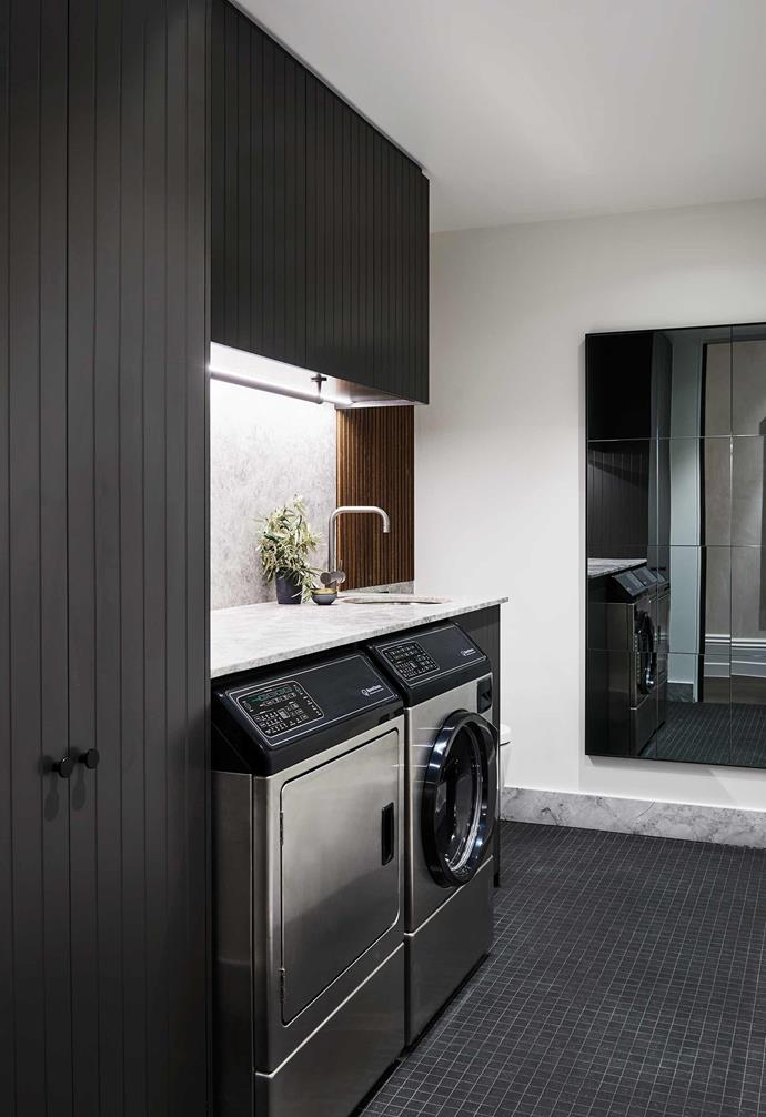 "**Washing zone** The [laundry space](https://www.homestolove.com.au/laundry-renovations-4-clever-layouts-that-work-14391|target=""_Blank"") sits beside the stairwell with a dark colour palette echoing that used in the kitchen."
