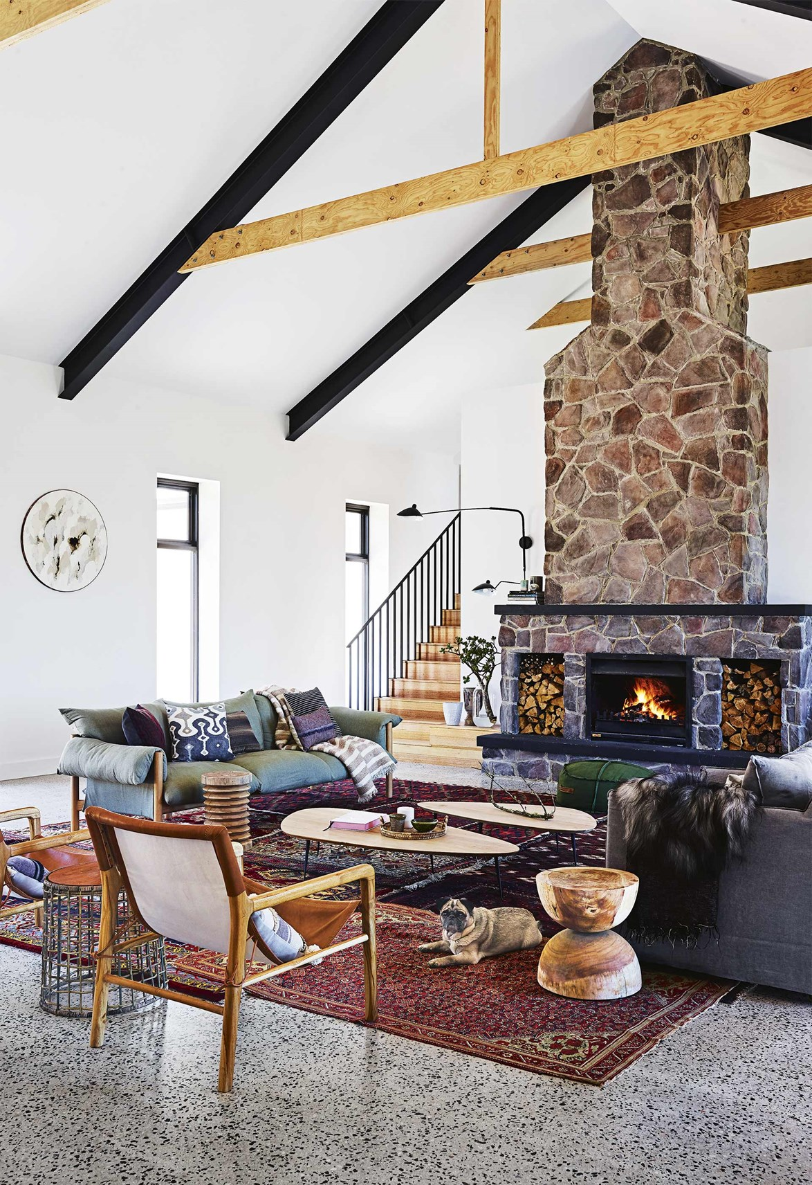 "Peter and Tracy Fleming's lifelong dream was to build a [farmhouse on their property in Brook Downs](https://www.homestolove.com.au/step-inside-this-cosy-country-farmhouse-with-modern-interiors-17468|target=""_blank""). Luckily their interior-designer son, *Inside Out's* style editor Jono Fleming, along with Green Apple Interiors & Design, were around to help! The traditional farmhouse look has been re-imagined here with matte black surfaces, timber and steel cathedral ceilings and a stone fireplace. *Photo: Anson Smart / Styling: Jono Fleming / Story: Inside Out*"