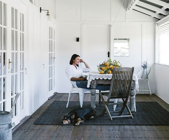 Maree Duncombe sitting in outdoor dining area with her dog