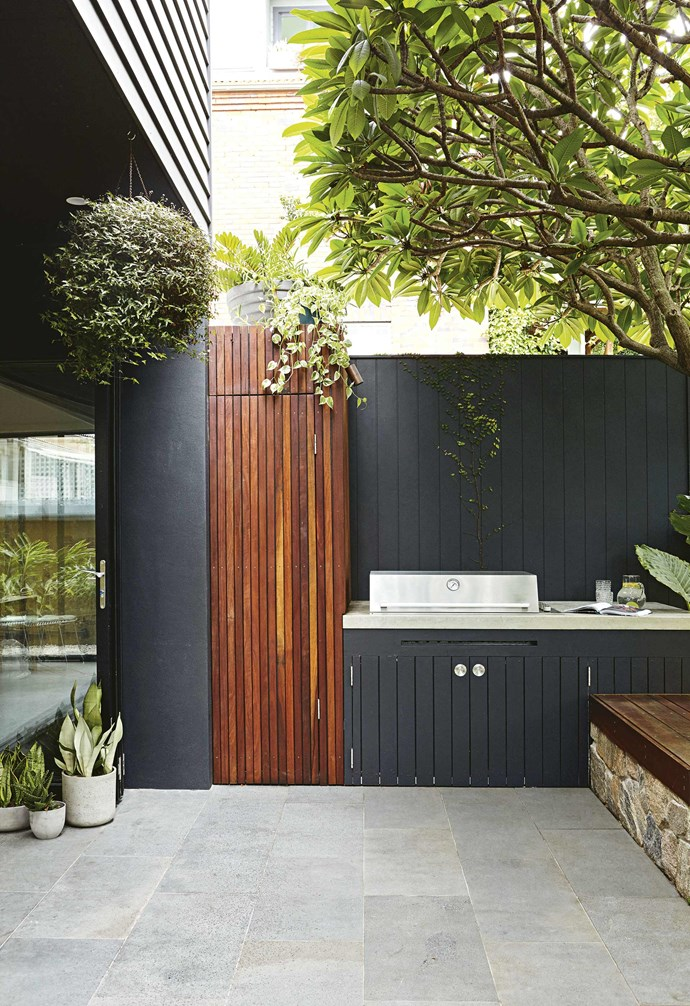 """Bluestone tiles trace a path to the pool, which is tiled in Ezarri 'Cocktail' tiles in Grasshopper. The cascading water feature is an addition Josh says is always popular with kids. """"They're a cost-effective way of adding a fun element to the pool,"""" he says.<br><br>A planter box clad in 'Howqua Free Form' granite from [Eco Outdoor](https://www.ecooutdoor.com.au/