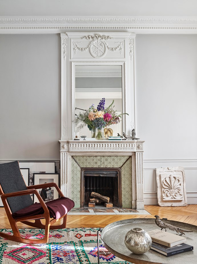 The couple have made the fireplace a focal point of their living space, dotting treasured trinkets along its mantel and leaning framed pictures and an antique moulding against the walls on either side.