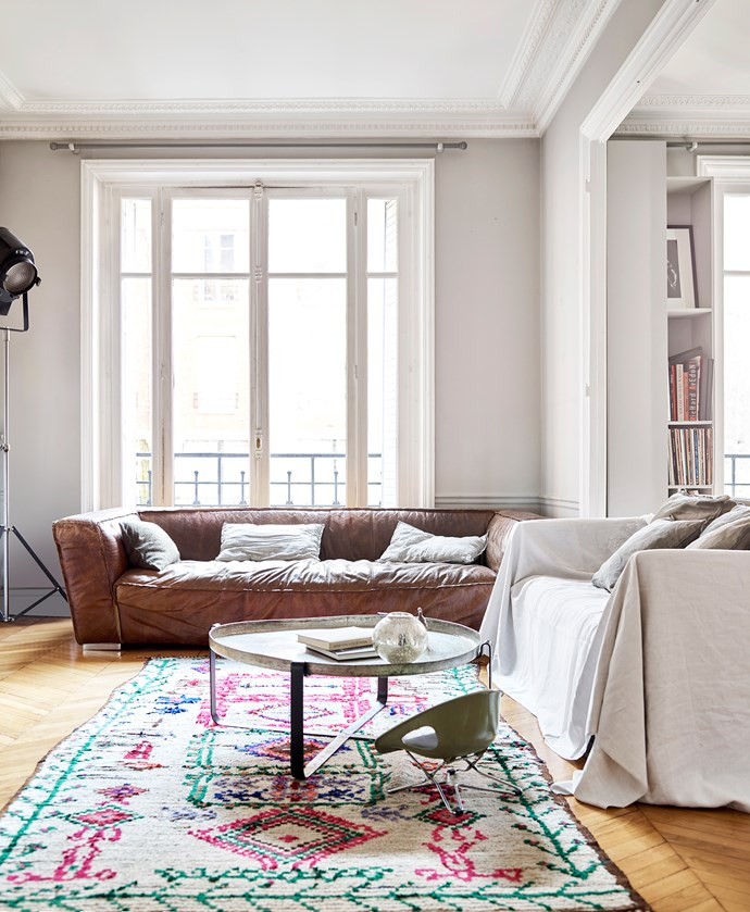 An extra-large leather couch, Tunisian coffee table from Zaama, azilal rug from Marrakesh, vintage child's car seat and old cinema lamp bring charm and character to the living room.
