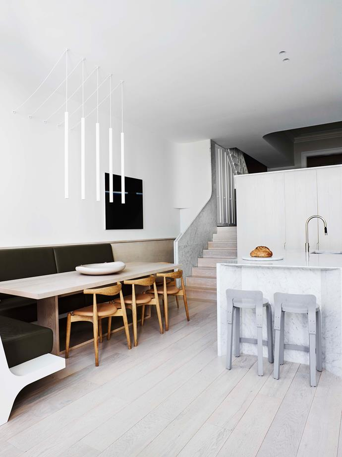 Custom pendant lights hang above the built-in bench seat and dining table with Carl Hansen + Søn 'Elbow' chairs from Cult.