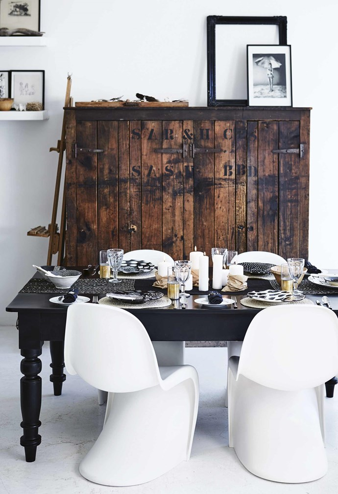"**Setting the table** Shelley's dining area shows how a [monochromatic interior](https://www.homestolove.com.au/11-style-ideas-from-a-monochrome-apartment-18693|target=""_blank"") can be warm, engaging and characterful with the inclusion of vintage, organic and rustic elements. Layered place settings of beaded placemats and patterned hand-crafted plates are teamed with a relaxed centrepiece of pillar candles wrapped in brown paper sitting on a black-and-white table runner. White Panton chairs introduce a modern classic touch in this [perfect Christmas table setting](https://www.homestolove.com.au/preview/christmas-table-setting-steps-16141