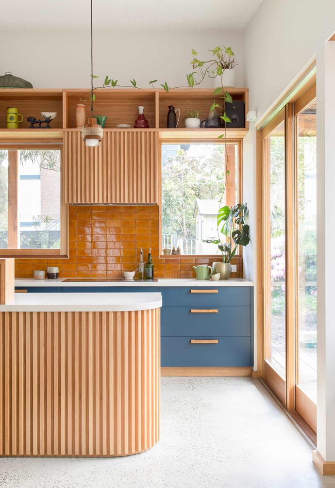 "**What's cooking?** A range of different textures sing in this timber kitchen space with glossy amber subway tiles forming the splashback. Blue [cabinetry](https://www.homestolove.com.au/kitchen-cabinets-your-guide-to-choosing-right-5610|target=""_blank"") features timber handles that echo the rest of the space and [white benchtops](https://www.homestolove.com.au/kitchen-benchtop-guide-19237
