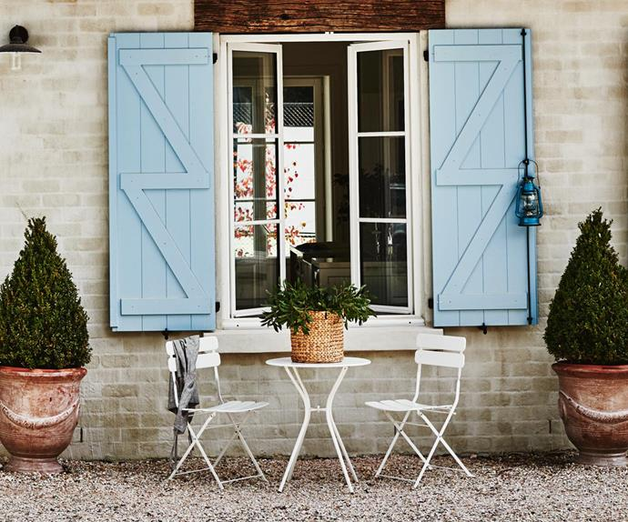 White outdoor dining setting in front of a farmhouse with blue window shutters