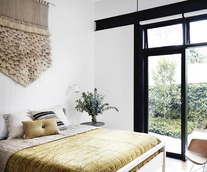 **Bedroom** A large tassel wall hanging makes an eye-catching artwork in the guest room, also home to a pretty velvet and linen bedspread and vintage Eames rocking chair.