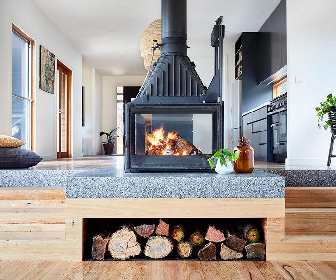 "**Heart of the home**  An industrial-style [fireplace](https://www.homestolove.com.au/15-fireplaces-we-want-to-curl-up-in-front-of-16870|target=""_blank"") is suspended from the ceiling and becomes the heart of the living room. Speckled [concrete flooring](https://www.homestolove.com.au/a-guide-to-concrete-flooring-16194