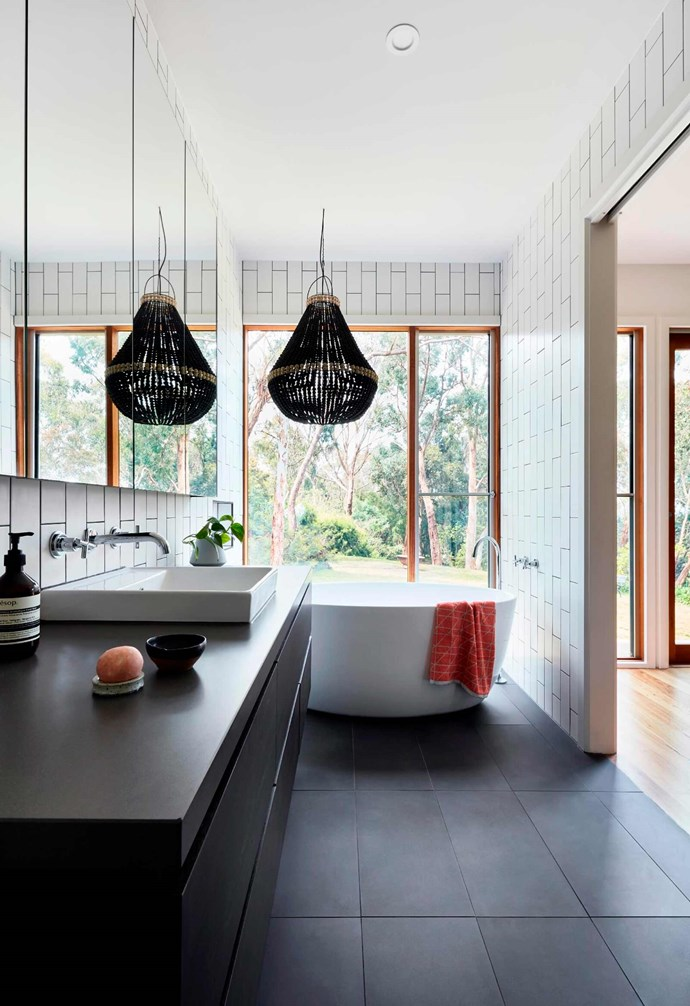 "**Bathroom** A woven pendant lamp hangs over a generous white [freestanding bathtub](https://www.homestolove.com.au/freestanding-baths-4520|target=""_blank"") in this bathroom. Large format black tiles are used for the flooring and are contrasted with vertical white subway tiles on the wall. The basin is built into black cabinetry for the vanity.  *Design: [Bryant Alsop](https://www.bryantalsop.com.au/