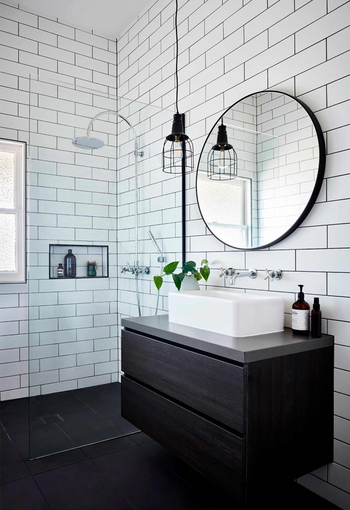 "**Bathroom** White subway tiles are laid horizontally in this smaller bathroom, with the same large format black tiles on the floor. A circular mirror sits above a white basin and black timber vanity, with an industrial-style pendant lamp hangs above.  *Design: [Bryant Alsop](https://www.bryantalsop.com.au/|target=""_blank""