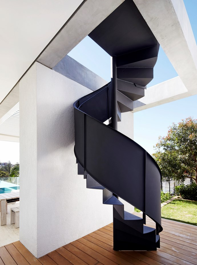 """A sweeping spiral staircase painted in Dulux 'Ferrodor' enamel leads up to the main bedroom balcony at a [luxurious contemporary home](https://www.homestolove.com.au/luxury-home-puts-a-contemporary-spin-on-classical-lines-3374