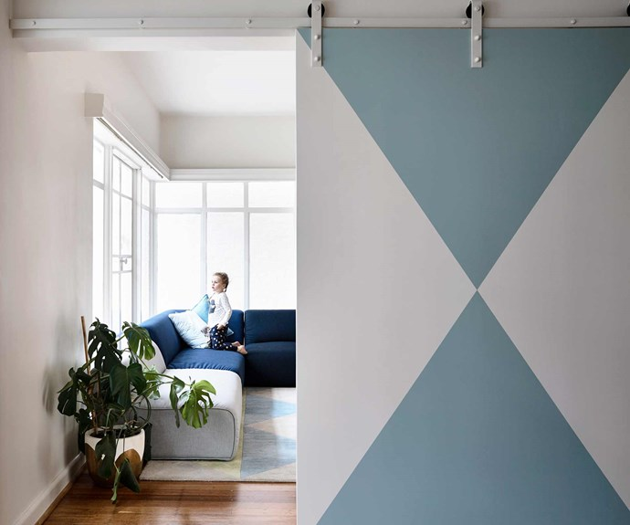 """**Play room** This [living space](https://www.homestolove.com.au/20-best-open-plan-living-designs-17877 target=""""_blank"""") can function as a cordoned off playroom for the kids thanks to a patterned painted [barn door](https://www.homestolove.com.au/barn-doors-the-latest-interior-obsession-17386 target=""""_blank""""). *Design: [Kennedy Nolan](http://www.kennedynolan.com.au/ target=""""_blank"""" rel=""""nofollow"""")   Photography: Derek Swalwell*."""