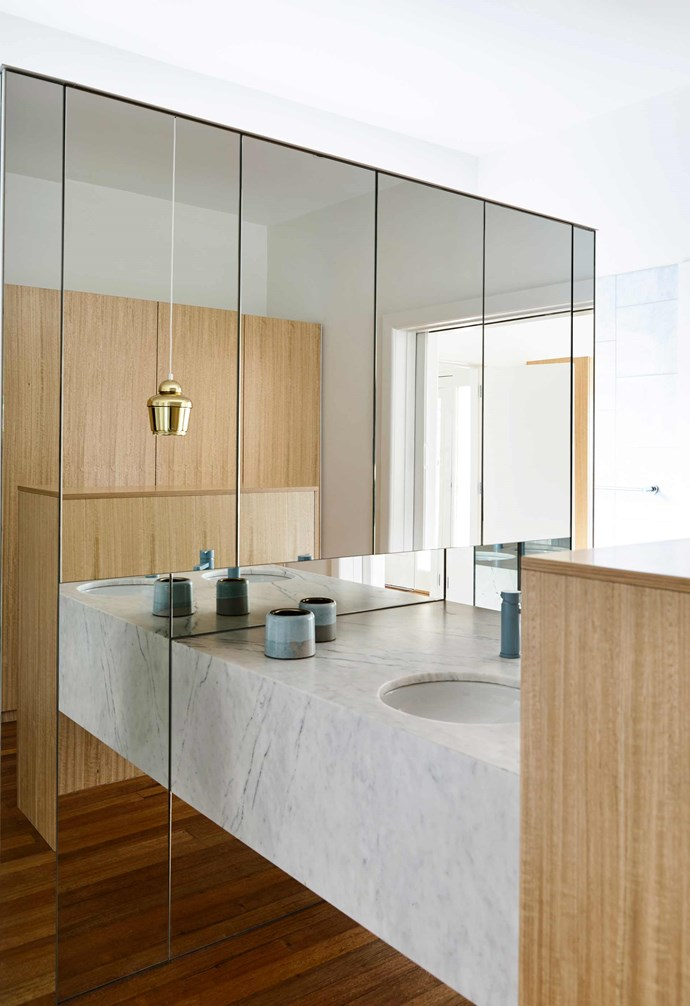 "**Bathroom** A simple brass pendant lamp adds a touch of luxe to this small [bathroom space](https://www.homestolove.com.au/15-bathrooms-with-clever-ideas-to-steal-18869|target=""_blank""). Mirrors play a major role in making the space feel larger, and timber cabinetry complements the stone vanity. *Design: [Kennedy Nolan](http://www.kennedynolan.com.au/