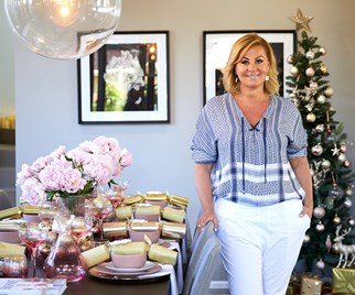 Chyka Keebaugh standing beside a table styled with Kmart Christmas decorations