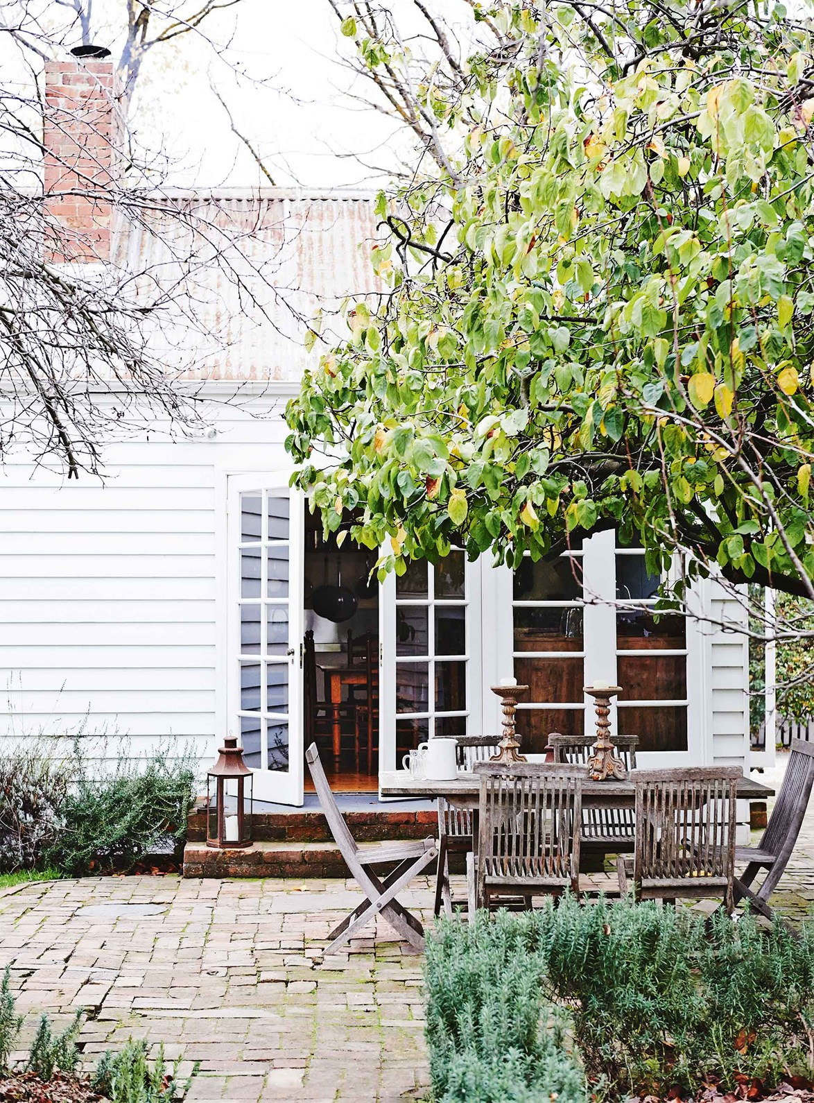 "The French doors of this [white weatherboard cottage](https://www.homestolove.com.au/white-weatherboard-cottage-victoria-13741|target=""_blank"") open to the rustic garden patio where each autumn, the owner invites friends to enjoy dishes made from the orchard's quinces."