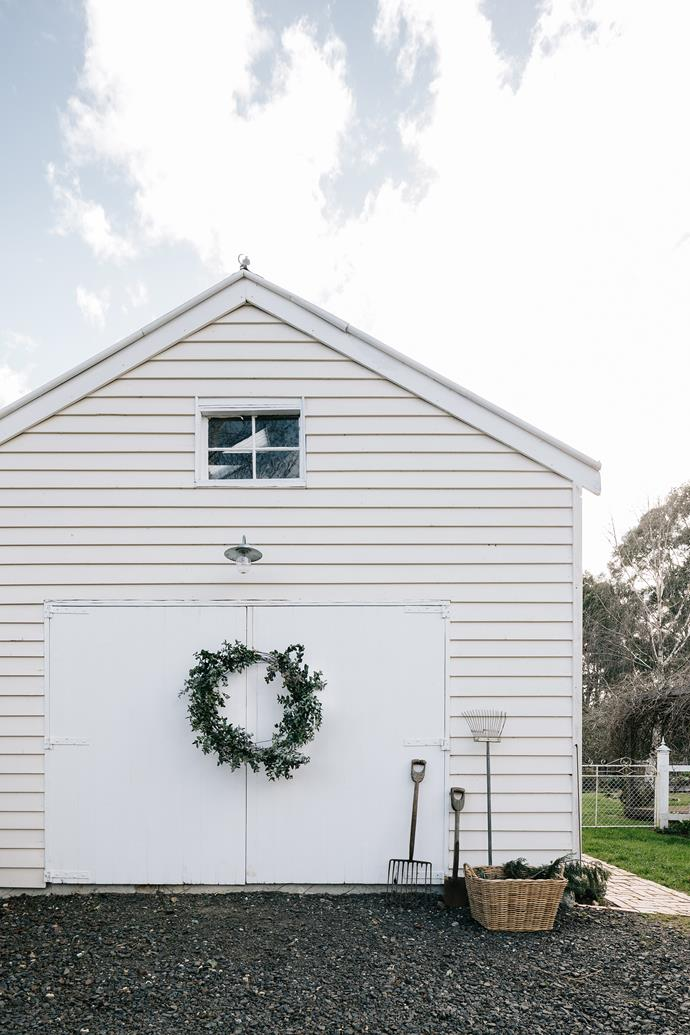 "There's an elegant driveway up to this versatile space. Hanging on the door is a wreath made from foraged eucalyptus branches by [Acre of Roses](https://www.homestolove.com.au/flower-farm-property-victoria-18945|target=""_blank""). The antique tools are purely decorative pieces."