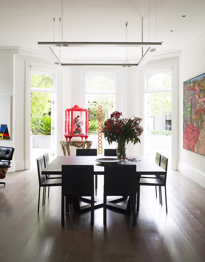 "A light handed approach to colour has been adopted in the dining room of a Sydney home designed by [Smart Design Studio](https://www.homestolove.com.au/a-le-corbusier-inspired-home-in-sydney-by-smart-design-studio-5024|target=""_blank""). A decorative bird cage and artwork introduce shades of living coral. *Photo: Anson Smart / Styling: Andrea Millar*"