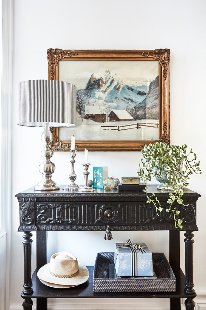 """In this vignette by the entrance, an artwork by Stephen's aunt, a pair of candlesticks that were a wedding present and a much-loved lamp are teamed with a [console table](https://www.homestolove.com.au/high-and-mighty-how-to-choose-the-perfect-console-table-2922