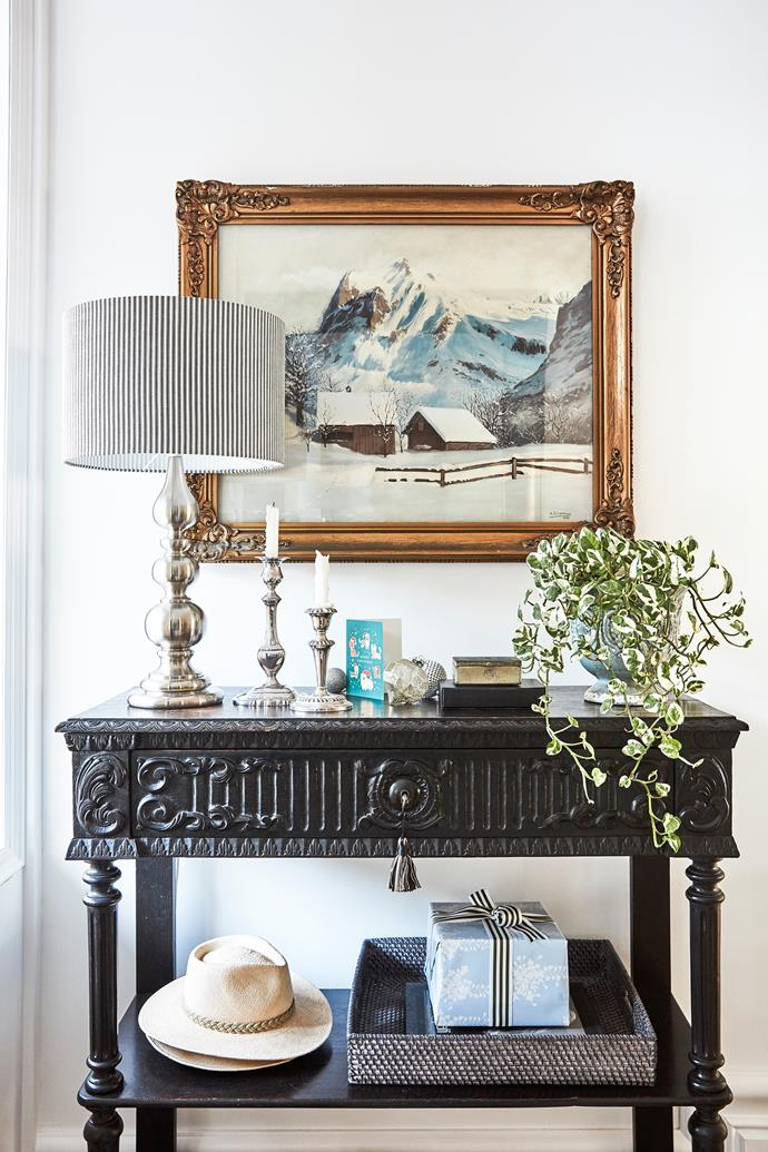 "In this vignette by the entrance, an artwork by Stephen's aunt, a pair of candlesticks that were a wedding present and a much-loved lamp are teamed with a [console table](https://www.homestolove.com.au/high-and-mighty-how-to-choose-the-perfect-console-table-2922|target=""_blank"") Judy found by the side of the road and restored."