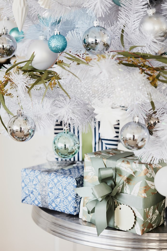 Beneath the Christmas tree, gifts are wrapped in a selection of paper and ribbon from Finmark, Fox & Fallow, Koch & Co and Vandoros Fine Packaging.