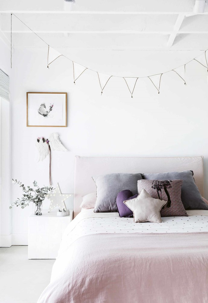 """Creating a relaxed feeling was important to Anna when she approached the design. """"I wanted a home where you could switch off from daily life,"""" she says. """"My husband travels a lot and needs to be able to unwind.""""<br><br>**Anoushka's room** A mix of Montmartre, Jardan and Mamapapa bedlinen creates a sweet combination under the MCM House bedhead and cushions. A 'Star' light from Coast To Coast sits under a painting by Jo Bertini. Artwork: Jo Bertini."""