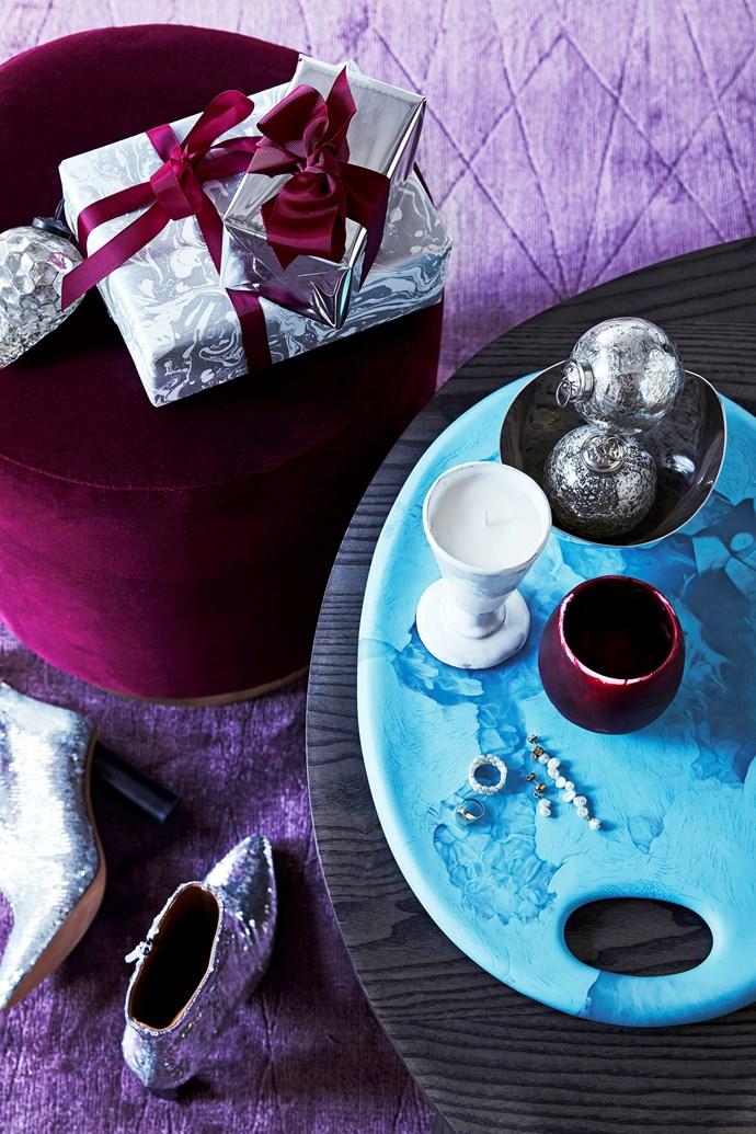 "De La Espada ""Kim"" nesting table, from $2690, Spence & Lyda. Taylor ottoman in Velvet Burgundy, $590, Fenton&Fenton. Large Resin Temple tray in Powder Blue, $350, Large Resin  Rock cup in Raspberry Dark, $95, and Medium Cloud bowl in Silver Plated, $190, Dinosaur Designs. Carron candle, $159, Maison Balzac. Silver Mercury Hanging Decoration balls, $3.50 each, Horgans."