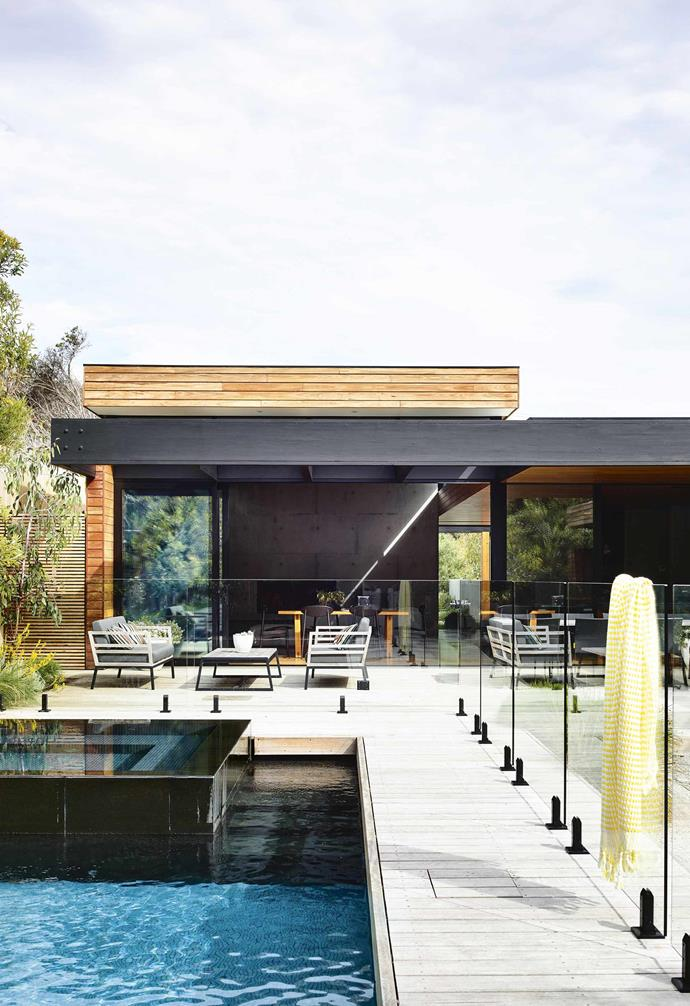 "The decks, designed to contribute to the coastal aesthetic, are constructed of large-profile blackbutt, which will silver up to the colour of driftwood and blend with the gravel pathways. The planting also matches the beach house vibe. The local council mandates a percentage of [plantings be indigenous to the area](https://www.homestolove.com.au/native-coastal-garden-plants-4685|target=""_blank""), so as well as the banksia on the fence line, succulent Carpobrotus rossii acts as groundcover, while Poa and Lomandra form grassy mounds.<br><br>**Pool & entertaining area** Subtle layers draw the eye across the outdoor area, making the space feel larger than it is. Each zone provides multiple functions, from the water-feature pool tiled in [Swimple tiles](http://www.swimple.com.au/