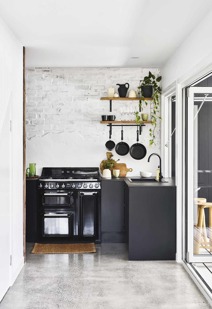 "**Kitchen** The black exterior is echoed in the compact kitchen, with an impressive Smeg oven setting the colour scheme for the rest of the space. Entrance mat, [Armadillo&Co](https://armadillo-co.com/|target=""_blank""