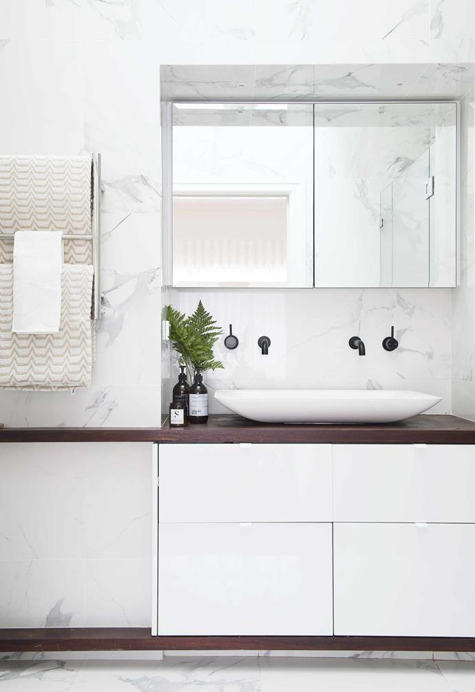 "**Bathroom** Marble-look porcelain tiles from Tiles Expo form the backdrop to custom cabinetry by Leon House Design, with a jarrah wood benchtop providing the setting for a Marblo basin and Astra Walker tapware. Heated Towel rail, [Reece](https://www.reece.com.au/|target=""_blank""