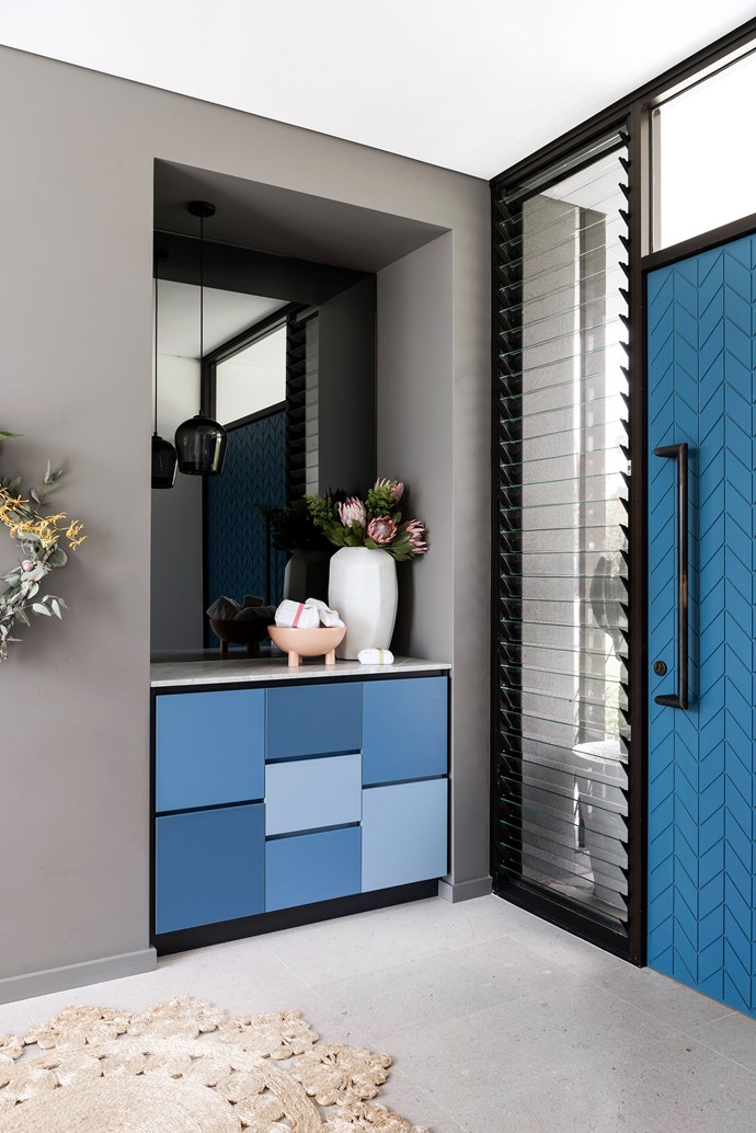 Blue and grey hues are paired throughout. The front door opens to a Mondrian-style arrangement of Laminex panels.