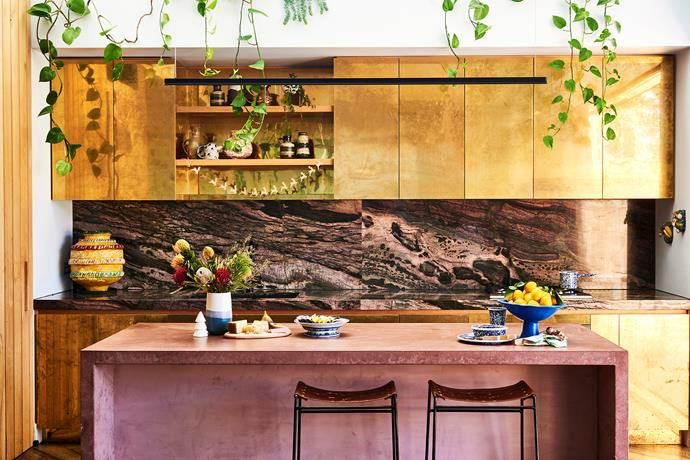 Alex's kitchen features a specially mixed pink concrete island, bamboo crocodile quartzite splashback, bespoke Jason Blake stools and brass cabinets that she and Bobby aged themselves using apple cider vinegar. Indoor plants trail down from an internal garden built above the cabinetry.